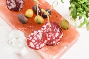 Salzblock, Salzplatte, garniert mit Salami